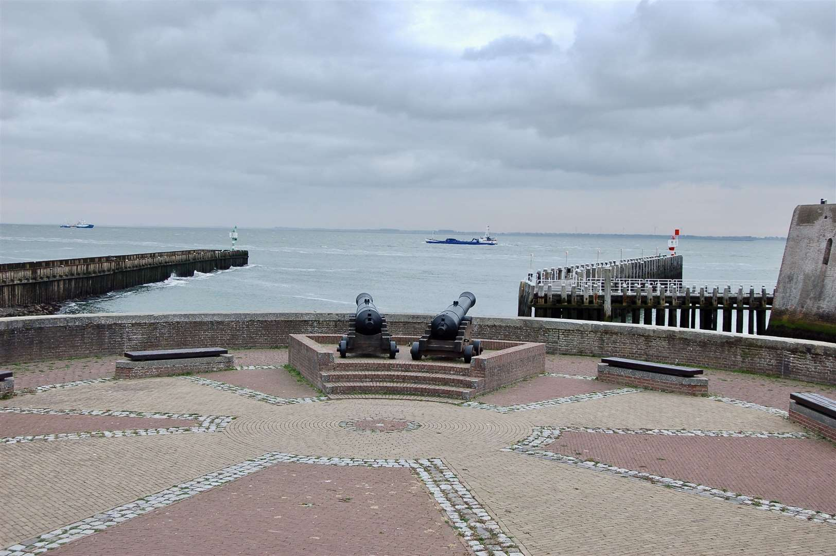 Old cannons still guard the harbour entrance as ships pass going to Antwerp.