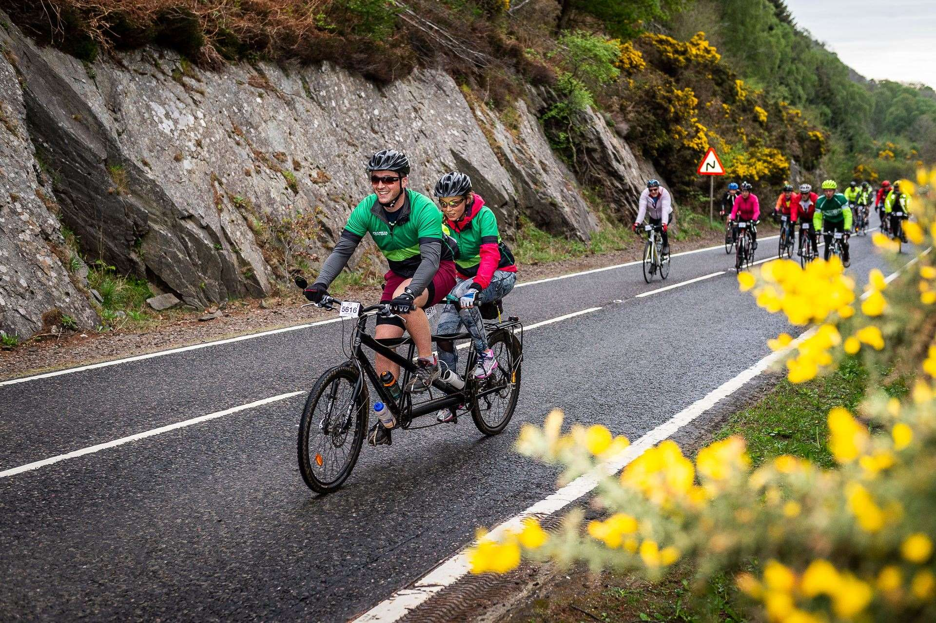 A pair of Macmillan Cancer Support cyclists riding a tandom bike as part of the Etape Loch Ness.