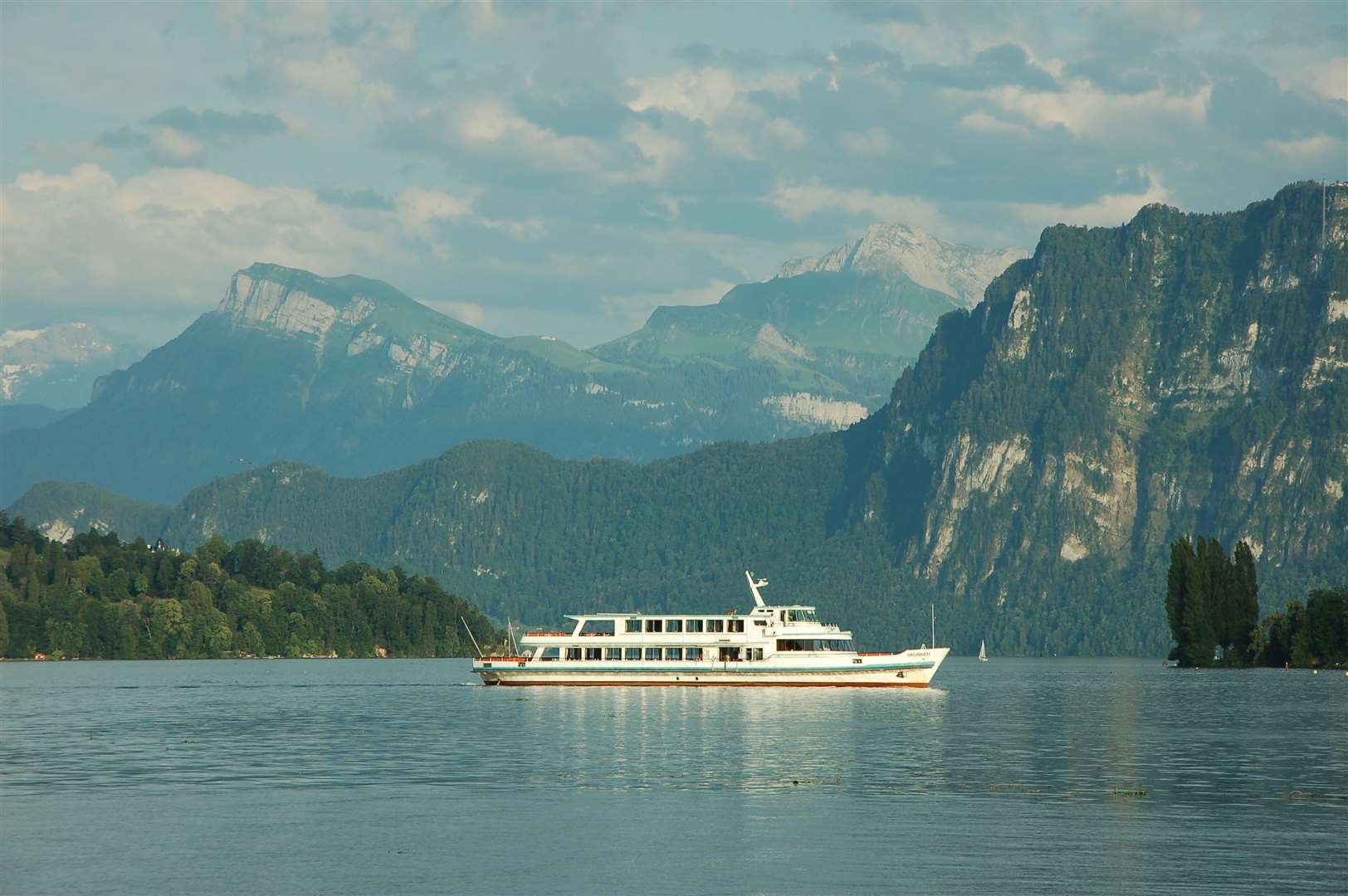 The majestic scenery and clear blue waters of the lake reflect on the MV Brunnen as it comes back to Luzern from a trip down the lake.